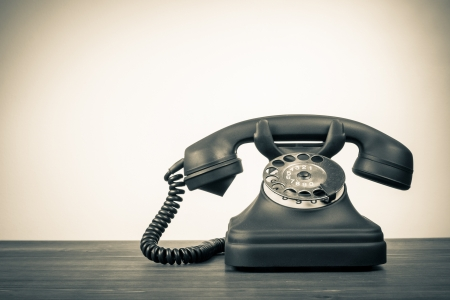 21797438 - retro rotary telephone on table with empty place for vintage background