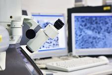 Mikroskop vor zwei Bildschirmen